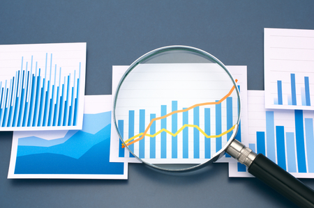 lupa: Analizando los datos con lupa. Muchos gráficos y lupa sobre fondo azul oscuro.