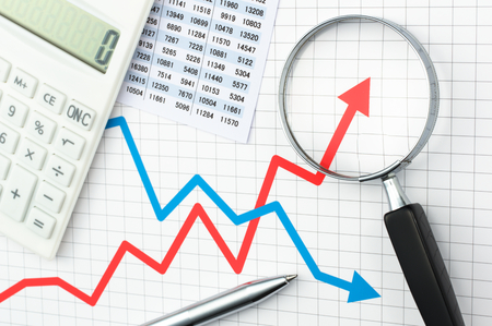 Line graph and magnifying glass. Analyzing data. Graph chart magnifying glass calculator and pen. Looking growth field of line graph with magnifying glass. Archivio Fotografico
