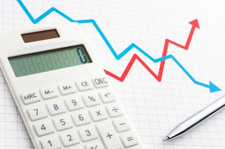 計算しグラフと計画。電卓とペンを線グラフの背景に。 写真素材
