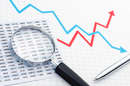 Making graph. Analyzing data with magnifying glass. Chart graph magnifying glass and pen on the line graph. Stockfoto