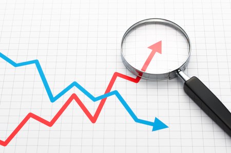 Line graph and magnifying glass. Looking growth field of line graph with magnifying glass.