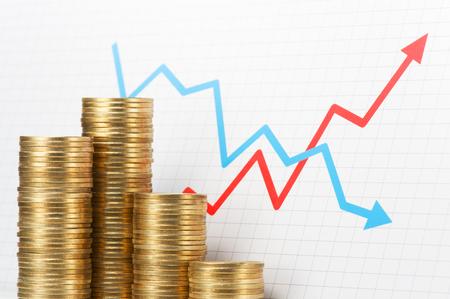 コインやグラフの山。資産管理.逆さまに成長し、矢印グラフの低下の欠点の 500 円硬貨の山。 写真素材