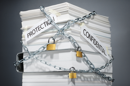 filing document: Data security. Protected documents. Confidential information. Locked pile of documents and folder. Gray background. Stock Photo