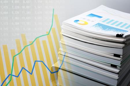 ドキュメントおよびデータの分析。ビジネス コンセプトです。灰色の背景に書類の山。グラフとモニター表示上のデータ。