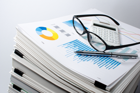 information analysis: Data management. Document management... Business concept. Pile of documents on gray background. Graph, glasses, calculate and pen.
