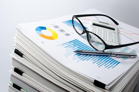 Gestión de datos. La gestión de documentos ... Concepto de negocio. La pila de documentos sobre fondo gris. Gráfica, vasos, calcular y pluma.