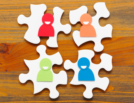 four people: Four paper people discussing. Concept image of meeting and teamwork. Four puzzle pieces and paper people. Wooden background.