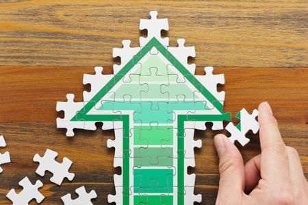 ジグソー パズルの形をした矢印を作るします。 成長戦略を開発のコンセプト イメージ。ジグソー パズルのピースと木製の背景に手。 写真素材