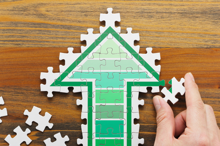 Making arrow shaped jigsaw puzzle.  Concept image of developing growth strategy. Jigsaw puzzle pieces and hand on wooden background. Stock Photo - 53658804