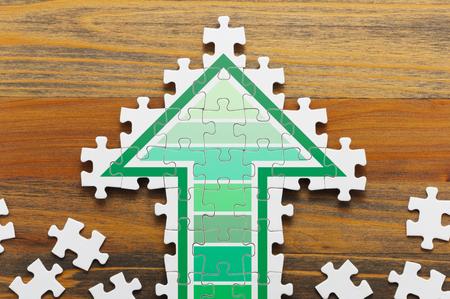 화살표 모양의 지 그 소 퍼즐. 성장 전략을 만드는 컨셉 이미지. 나무 배경에 지 그 소 퍼즐 조각입니다. 스톡 콘텐츠