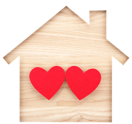 paper cutout: House shaped paper cutout and two hearts on natural wood lumber. Isolated on white background. Stock Photo