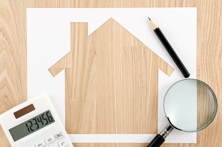 home planning: Home planning. Calculating and checking. House shaped paper cutout, calculator and magnifier on wood lumber.