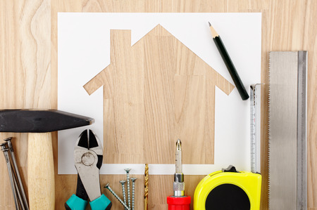 home planning: Home planning and preparing. House shaped paper cutout and tools on wooden table.