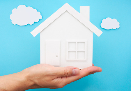 hand holding house: Hand holding house against sky made of paper. House shaped paper cutout on paper background.