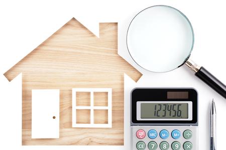 Casa en forma de recorte de papel, calculadora, lupa y una pluma en la madera de madera natural. Aislado en el fondo blanco.