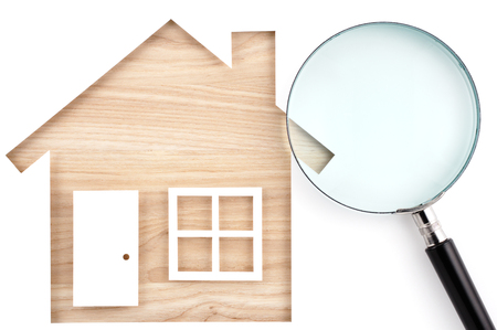 paper cutout: House shaped paper cutout and magnifier on natural wood lumber. Isolated on white background. Stock Photo