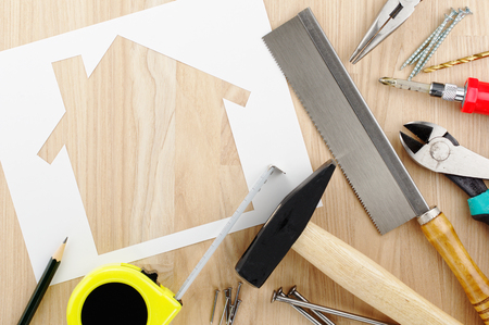 Home planning and preparing. House shaped paper cutout and tools on wood lumber.