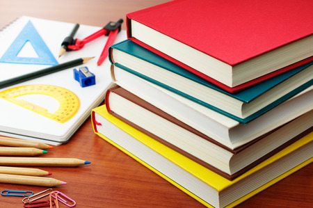 Studying and textbooks. Stack of colorful books, stationery and note on wooden desk.