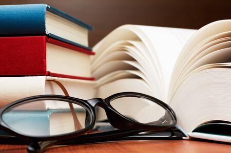 本、大きい本ページおよびガラスのスタックをクローズ アップ。ガラスと木製のテーブルの本。 写真素材