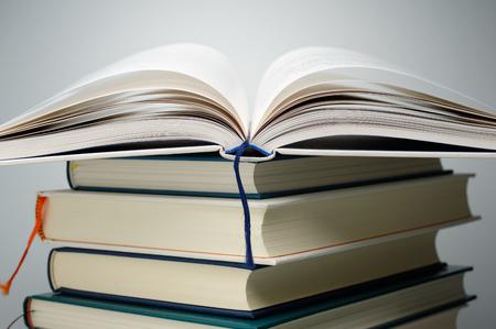 libros abiertos: Cerrar las páginas del libro abierto en la pila de libros. Pila de libros en el fondo gris. Foto de archivo