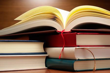 libros abiertos: La pila de libros y libro abierto sobre la mesa de madera. Cierre de libros y páginas del libro abierto. Foto de archivo