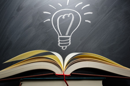 Studying and knowledge. Turn on the light bulb. Open book and light bulb drawn on blackboard Archivio Fotografico