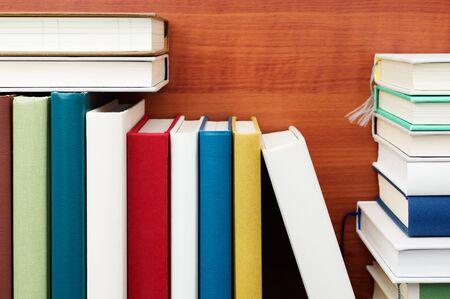 書籍。本棚のクローズ アップ。カラフルな本。木目の背景。 写真素材