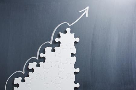 ジグソー パズルの形の手順はパズル、黒板上矢します。成長戦略を作るの概念イメージ。 写真素材