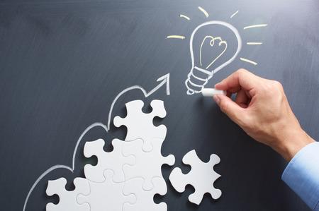 黒板の図面の電球。手順は形のジグソー パズルです。新しいアイデアを開発のコンセプト イメージ。