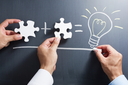 Solving puzzle together. Drawing light bulb on blackboard. Combining the wisdom for developing new idea. Stock Photo