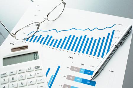 ビジネス文書の見直し。グラフとチャート。財務報告書、電卓、メガネ、ペン。