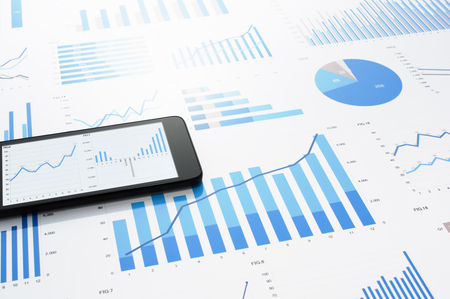 多くのチャートとグラフ。データ収集のコンセプト イメージ。会計データは、灰色の反射の背景にスマート フォン。 写真素材