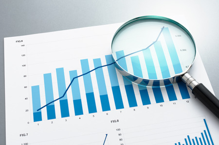 Document, charts and magnifying glass on gray reflection background. Reviewing business report. Looking at growth chart with magnifying glass.
