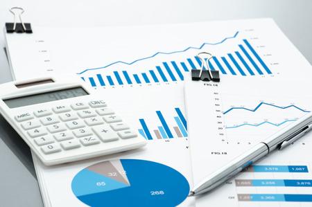 ビジネス文書、電卓、ペン グレー反射の背景に。有価証券報告書を確認します。論文・図の束。