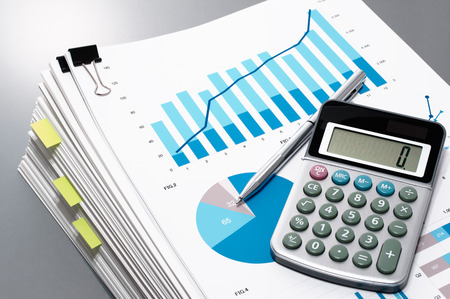 prepare: Pile of documents, calculator and pen on gray reflection background. Reviewing report. Many graphs and charts. Stock Photo