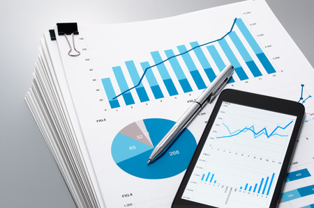 Pile of documents, smart phone and pen. Many graphs and charts. Concept image of data gathering.