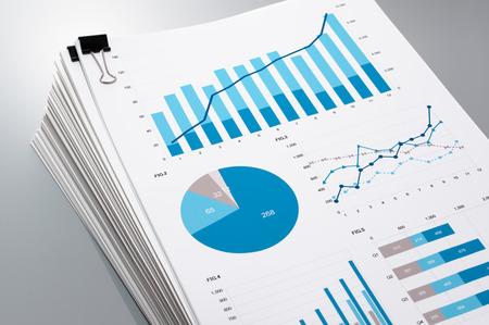 Stapel papieren op een grijze achtergrond reflectie. Vele grafieken en diagrammen. Concept imago van het verzamelen van gegevens. Stockfoto