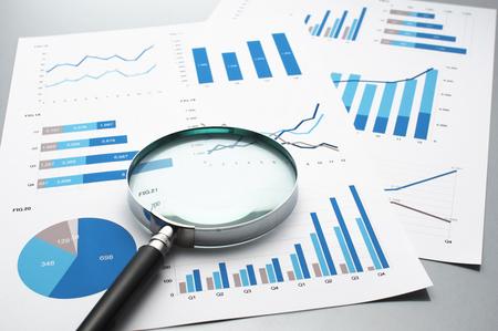 Bedrijfsrapporten herzien. Grafieken en grafieken. Financiële rapporten, documenten en vergrootglas.