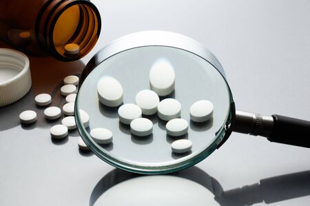 checking ingredients: Magnifying glass, tablets and bottle on gray reflection background. Checking ingredients and effectiveness of medicine.