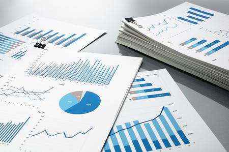 とりレポート。青いグラフとチャート。ビジネス レポートは、灰色の反射の背景上の書類の山。 写真素材
