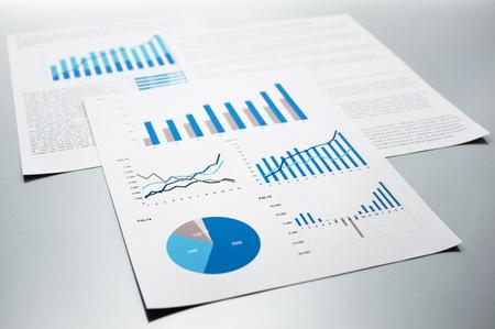 事業報告。グラフとチャート。灰色の反射背景上のドキュメント。