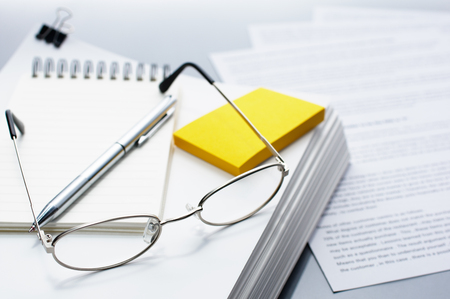 pile of documents: Checking and reviewing documents. Glasses, pen and pile of documents. Pile of documents on gray reflection background.