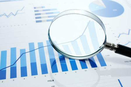 虫眼鏡で成長グラフを見てください。グラフ、グラフおよび反射の背景に虫眼鏡。