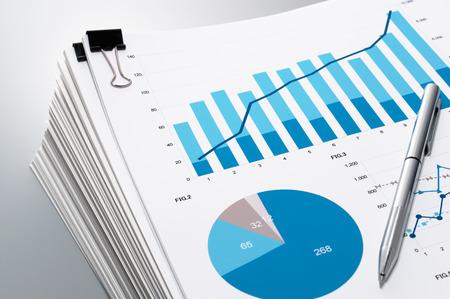 文書やグラフのクローズ アップ。ドキュメントおよび灰色の反射の背景にペンの山。