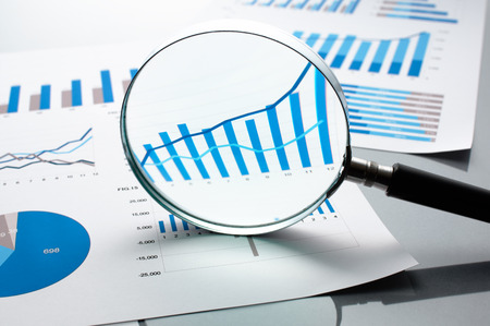 financial reports: Reviewing financial reports. Graphs and charts. Financial reports, documents and magnifying glass. Stock Photo