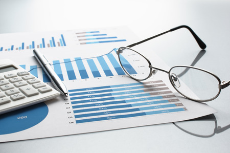 financial reports: Reviewing business report. Graphs and charts. Financial reports, documents, calculator, glasses and pen.