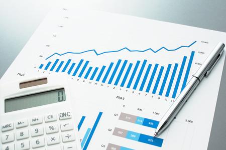 有価証券報告書を確認します。グラフとチャート。ビジネス文書、電卓、ペン。 写真素材