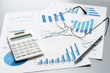 事業報告の内容を確認します。グラフとチャート。財務報告書、ドキュメント、電卓、メガネ、ペン。
