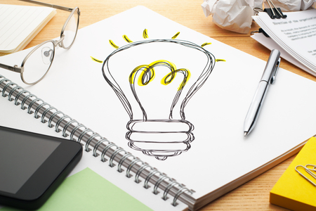 characterize: Turning on the light bulb. Drawing light bulb on notebook. Creating ideas. Notebook, pen, smartphone, glasses and the document on wood table. Stock Photo