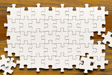 White puzzle pieces on wood background. Partially completed box shaped puzzle pieces. Banque d'images